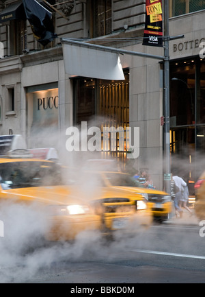 New York Street scene. Yellow cabs and steam on 5th Avenue - Stock Photo
