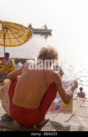 Holy man reading a newspaper. Main ghat, Varanasi, India. - Stock Photo