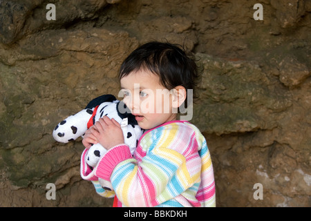 A young half-Thai girl cuddles her fluffy, spotty toy dog under a man-made rock arch at Skegness promenade, Lincolnshire - Stock Photo