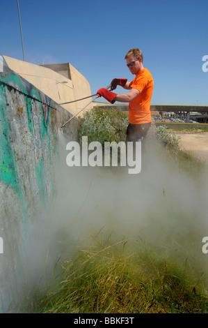 A man cleans up graffiti at Brighton marina using hot pressurized water - Stock Photo