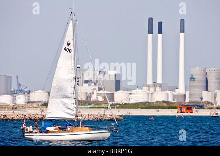 Sailboat in front of industrial harbour, Copenhagen, Denmark - Stock Photo