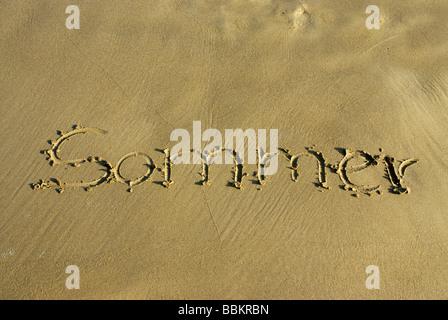 'Sommer', summer written in the sand - Stock Photo