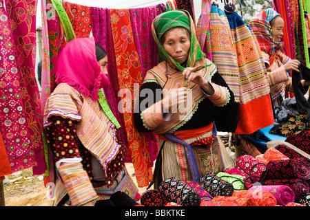 Flower Hmong women selling textiles in Can Cau Market north of Bac Ha In North Vietnam - Stock Photo
