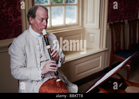A costumed historical interpreter plays a recorder in Colonial Williamsburg Virginia - Stock Photo
