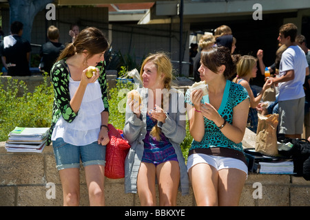 Three Southern California high school girls eat a healthy meal of fruit and turkey sandwiches during lunchtime on - Stock Photo