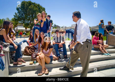 A Southern California high school principal enjoys talking with his students during lunchtime on campus Note skateboard - Stock Photo