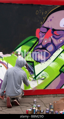 graffiti artist working on design in Bacon Street Shoreditch London UK - Stock Photo