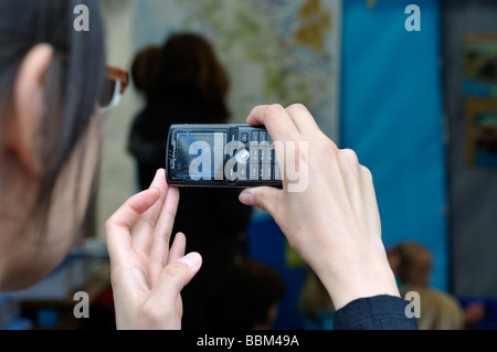 Closeup woman s hands holding mobile phone taking a photo - Stock Photo