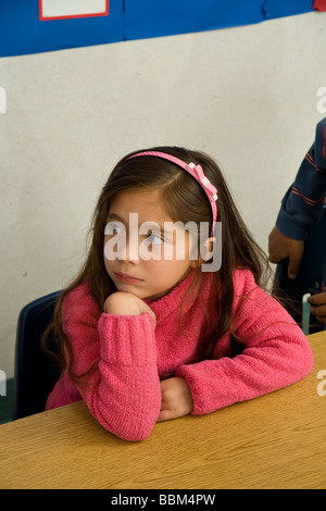 5-6 year old student multi ethnic racial diversity racially diverse multicultural Hispanic girl classroom listening - Stock Photo