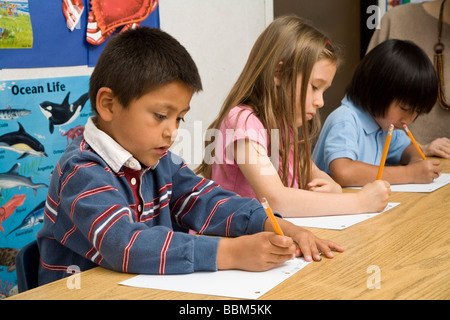 5-6 year old students multi ethnic inter racial diversity racially diverse multicultural cultural interracial write - Stock Photo