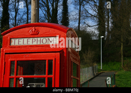 Close detail shot of a bright red telephone box against a blue and green background. - Stock Photo