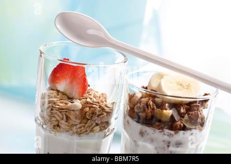 Muesli and chocolate muesli with yoghurt and in a small glass jar, sliced banana, strawberries, yoghurt spoon - Stock Photo