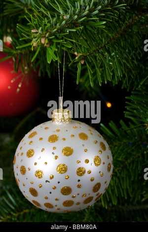 White and gold glass bauble on real Christmas tree branch - Stock Photo