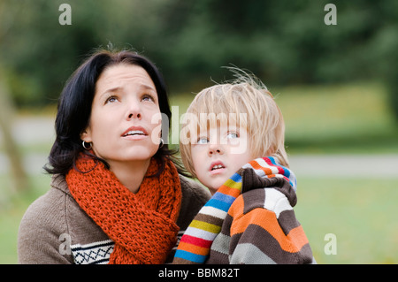Young woman and boy with concerned expressions looking upward, Vancouver, British Columbia - Stock Photo