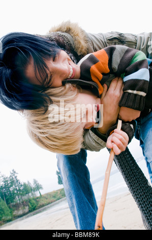 Woman embraces young son on beach, Vancouver, British Columbia - Stock Photo