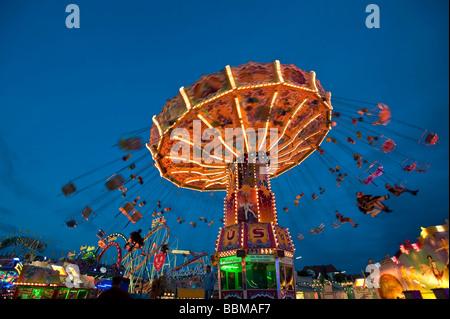 Illuminated Chairoplane at dusk, Oktoberfest festival, Munich, Bavaria, Germany - Stock Photo