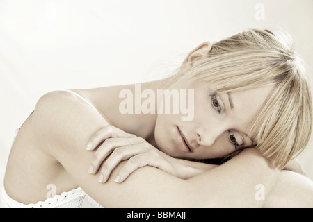 Pretty young woman leaning her head on her arms - Stock Photo