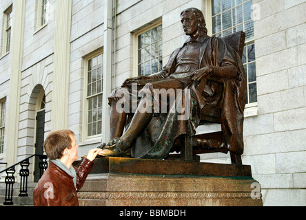 Student at the John Harvard statue by Daniel Chester French, the touch of the shoe will bring luck in exams, Harvard - Stock Photo