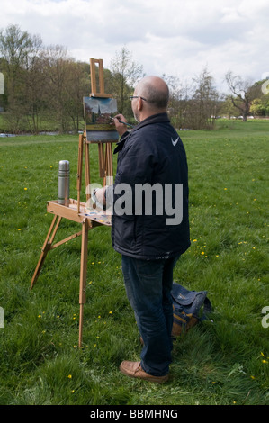 Artist/Painter painting picture on easel in the Derbyshire countryside near Bakewell England UK - Stock Photo