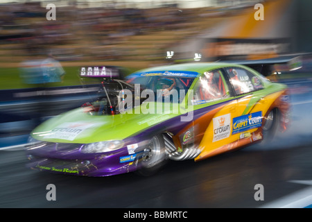 Australian drag racer, Maurice Brennan, performing a burnout in his heavily modified Holden Commodore Top Comp race - Stock Photo