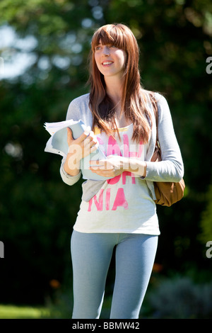 Girl walking with books - Stock Photo