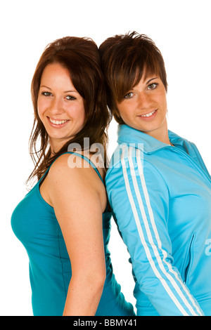 Two young women standing back to back - Stock Photo