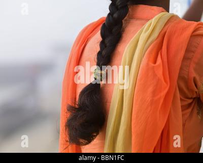 Varanasi,India;Rear view of an Indian woman wearing a vibrant orange sari - Stock Photo