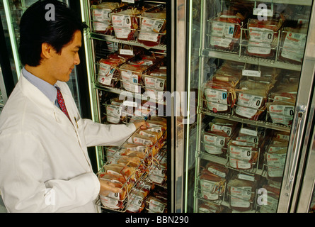 Technician pulling supply from refrigerated blood bank storage - Stock Photo