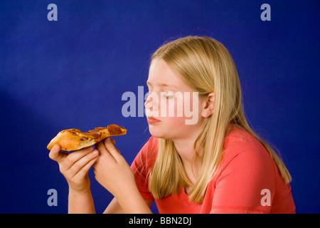 Portrait of girl eating slice of pizza, studio shot cut out MR  © Myrleen Pearson