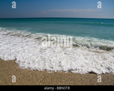 small waves wash up on shore at beach - Stock Photo