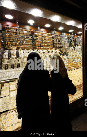 Two Turkish women looking at gold jewelry in a shop window, one with headscarf, the other with traditional full - Stock Photo