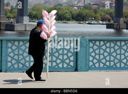 Street vendorswith candy floss on a pole walking over a bridge, Golden Horn, Istanbul, Turkey - Stock Photo
