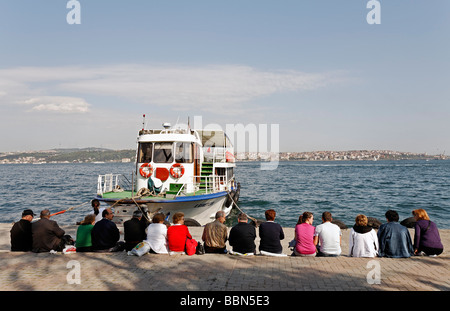 People sit in a row on the quay, waiting for the ferry, Bosphorus panorama, Kabatas, Istanbul, Turkey