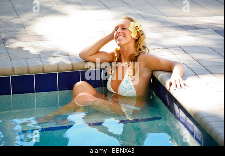 Young white blonde woman relaxing in an outdoor hot tub on vacation at a spa. - Stock Photo