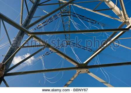 high voltage transmission tower pylon energy electricity overhead cable connection engineering worm's-eye view Germany - Stock Photo