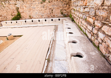 Ancient roman latrine public toilets at Ephesus in Turkey - Stock Photo