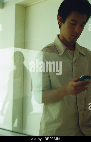 Male text messaging, reflection of female in window - Stock Photo