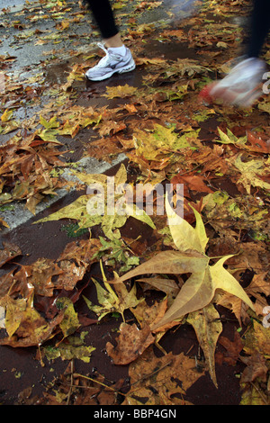 two fast runners in action on leaf covered street in countryside - Stock Photo