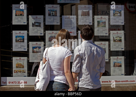 First time buyers looking at houses for sale in an estate agents window - Stock Photo