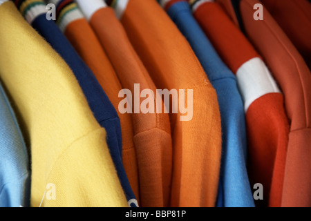 Close up of clothes on a rail in vintage secondhand shop - Stock Photo
