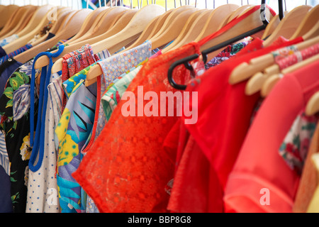 clothes on hangers in vintage secondhand shop - Stock Photo