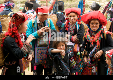 A  group of women and children wearing traditional costume from the Red Dao tribe in Sapa Northern Vietnam - Stock Photo