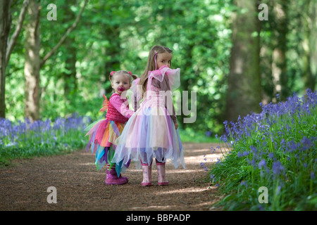 Two young children dressed as fairies exploring bluebell filled woodland in England. - Stock Photo
