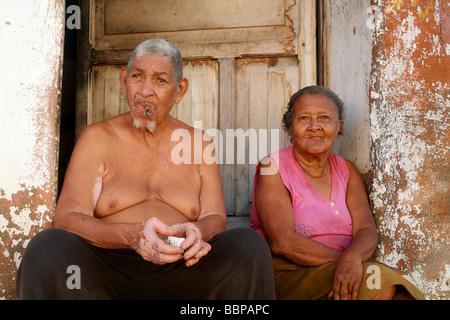 A cuban couple sat on their doorstep - Stock Photo