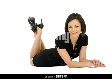 Studio portrait of a pretty young brunette woman wearing a short black dress and high heeled shoes - Stock Photo