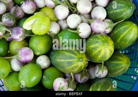 Cucumber aubergines and limes at the daily food market in Luang Prabang Laos - Stock Photo
