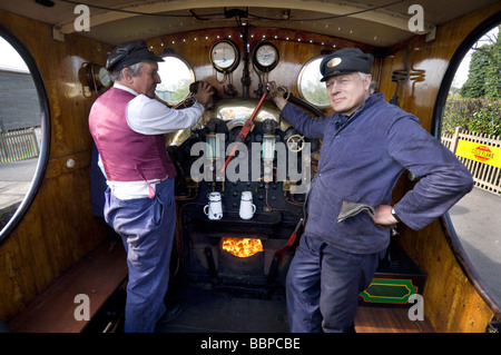 An engine driver and firemen at the Bluebell Railway, a preserved rail line in Sussex  England. - Stock Photo