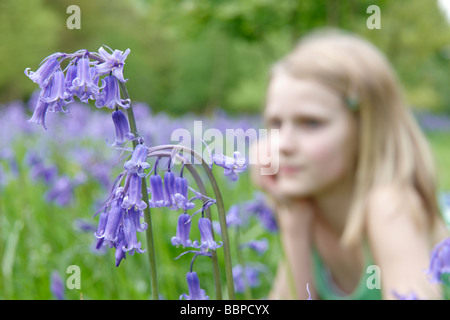close up of bluebells with young girl out of focus in background - Stock Photo