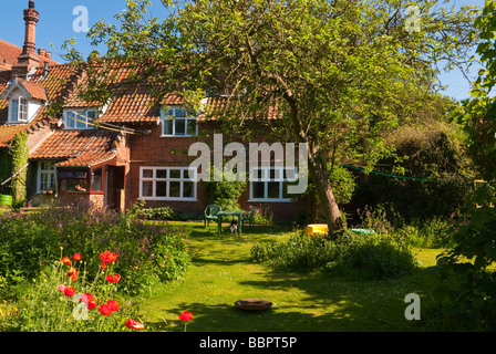 A lovely English country cottage in the spring with blooming garden and a view of a country life setting in Suffolk - Stock Photo