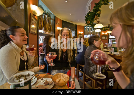 Three young women converse after a tapas lunch in a cafe in the downtown shopping district of Seville Spain - Stock Photo